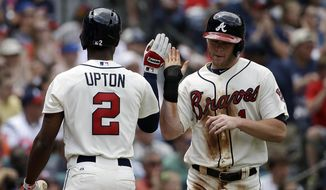 Atlanta Braves' Tyler Pastornicky, right, high-fives teammate B.J. Upton after scoring off a double by Jason Heyward in the second inning of a baseball game against the Washington Nationals, Sunday, April 13, 2014, in Atlanta. (AP Photo/David Goldman)