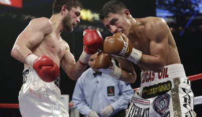 Khabib Allakhverdiev, left, from Russia, and Jessie Vargas, of the United States, trade punches in their WBA-IBO junior welterweight title boxing fight Saturday, April 12, 2014, in Las Vegas. Vargas went on to win the bout by unanimous decision. (AP Photo/Isaac Brekken)
