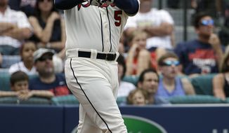 Atlanta Braves' Freddie Freeman hits a two-run home run to score teammate Jason Heyward in the second inning of a baseball game against the Washington Nationals, Sunday, April 13, 2014, in Atlanta. (AP Photo/David Goldman)