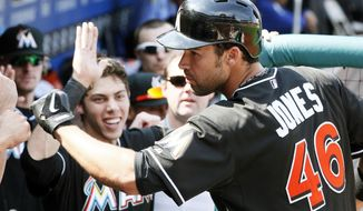 Miami Marlins' Garrett Jones, right, returns to high-fives in the dugout after hitting a solo home run during the fifth inning of a baseball game against the Philadelphia Phillies, Sunday, April 13, 2014, in Philadelphia. (AP Photo/Tom Mihalek)