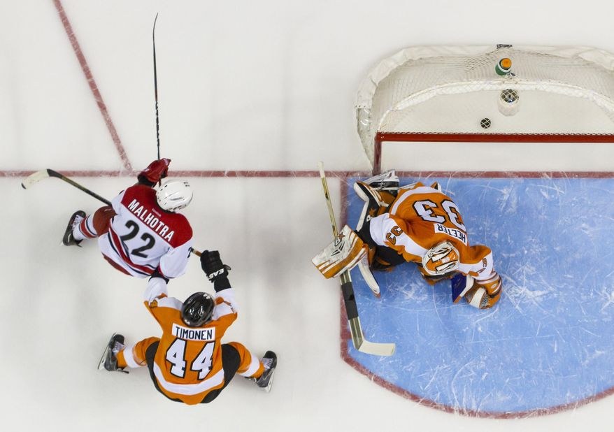 Carolina Hurricanes' Manny Malhotra, left, scores a goal on Philadelphia Flyers goalie Cal Heeter, right, as  Kimmo Timonen watches during the first period of an NHL hockey game, Sunday, April 13, 2014, in Philadelphia. (AP Photo/Chris Szagola)