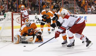 Philadelphia Flyers goalie Cal Heeter, left, reaches for a rebound in front of teammate Sean Couturier (14) and Carolina Hurricanes' Jeff Skinner during the first period of an NHL hockey game, Sunday, April 13, 2014, in Philadelphia. (AP Photo/Chris Szagola)