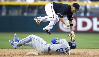 Los Angeles Dodgers' Yasiel Puig, bottom, slides safely into second base under the tag of Arizona Diamondbacks' Aaron Hill in the third inning of a baseball game on Saturday, April 12, 2014, in Phoenix. (AP Photo/The Arizona Republic, Rob Schumacher) MARICOPA COUNTY OUT; NO SALES