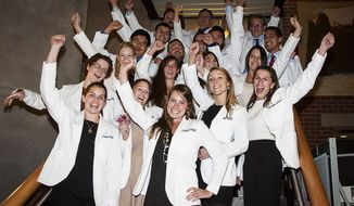 In this Sept. 20, 2013 photo from Washington State University, medical students celebrate at a 'white coat ceremony,' where they move from pre-clinical to clinical studies, at the WSU campus in Spokane, Wash.  Projecting a looming shortage of doctors in the state, Washington State is exploring the creation of its own medical school. The university has commissioned a feasibility study, due at the end of June, on whether a medical school in Spokane would succeed. (AP Photo/Washington State University, Cori Medeiros)