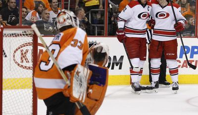 Carolina Hurricanes' Eric Staal, left rear, celebrates with Brett Bellemore after Staal scored against Philadelphia Flyers goalie Cal Heeter during the first period of an NHL hockey game, Sunday, April 13, 2014, in Philadelphia. (AP Photo/Chris Szagola)