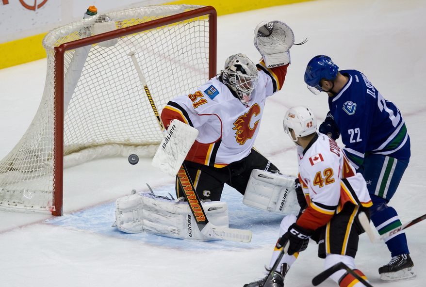 Vancouver Canucks' Daniel Sedin, right, of Sweden, tips the puck past Calgary Flames' goalie Karri Ramo, of Finland, for a goal as Flames' Mark Cundari (42) defends during first period NHL hockey action in Vancouver,British Columbia, on Sunday April 13, 2014. (AP Photo/The Canadian Press, Darryl Dyck)