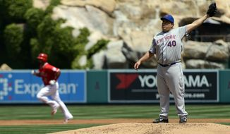 New York Mets starting pitcher Bartolo Colon, right, stretches to catch a ball after a home run was hit by Los Angeles Angels' Albert Pujols, left, during the first inning of a baseball game in Anaheim, Calif., Sunday, April 13, 2014. (AP Photo/Kelvin Kuo)