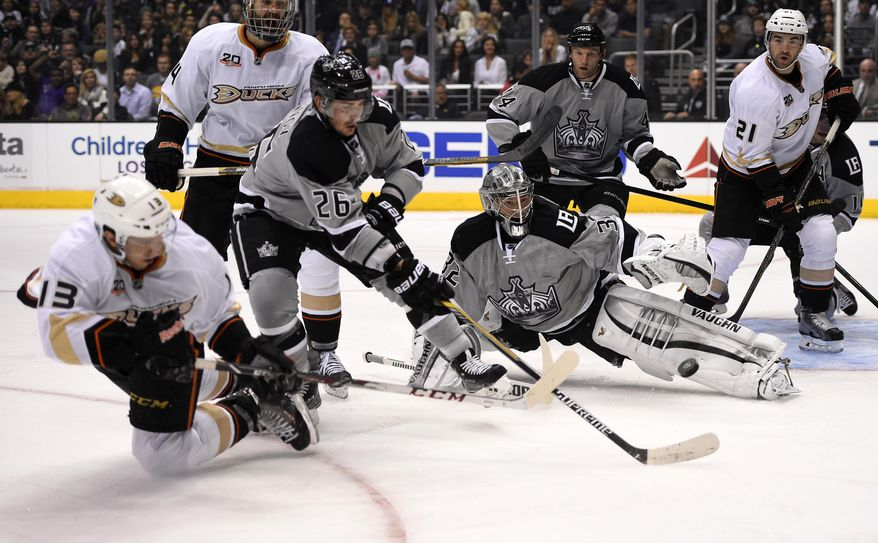 Anaheim Ducks center Nick Bonino, left, scores on Los Angeles Kings goalie Jonathan Quick, third from right, as right wing Daniel Winnik, second from  left, defenseman Slava Voynov, third from left, of Russia, defenseman Robyn Regehr, second from right, of Brazil, and right wing Kyle Palmieri look on during the first period of an NHL hockey game, Saturday, April 12, 2014, in Los Angeles.  (AP Photo/Mark J. Terrill)