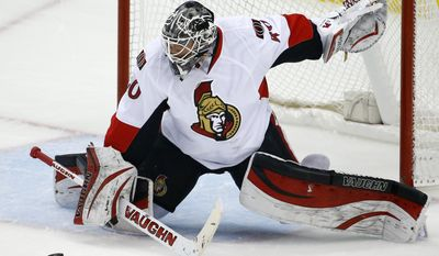 A shot by Pittsburgh Penguins' Jussi Jokinen nears Ottawa Senators goalie Robin Lehner before getting past for a goal in the first period of an NHL hockey game in Pittsburgh, Sunday, April 13, 2014. (AP Photo/Gene J. Puskar)