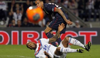 Lyon's Jimmy Briand, down, challenges for the ball with Paris Saint Germain's Gregory Van Der Wiel, up, during their French League One soccer match in Lyon, central France, Sunday, April 13, 2014. (AP Photo/Laurent Cipriani)