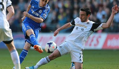 Chelsea's Oscar., left,  is tackled by Swansea City's Leon Britton during their English  Premier League match at the Liberty Stadium, Swansea Wales Sunday April 13, 2014. (AP Photo/David Davies/PA) UNITED KINGDOM OUT