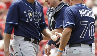 Tampa Bay Rays manager Joe Maddon (70) takes starting pitcher Cesar Ramos, left, out in the third inning of a baseball game against the Cincinnati Reds, Sunday, April 13, 2014, in Cincinnati. Catcher Ryan Hanigan watches. (AP Photo/Al Behrman)