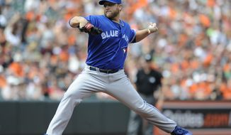 Toronto Blue Jays starting pitcher Mark Buehrle throws against the Baltimore Orioles in the first inning of a baseball game on Sunday, April 13, 2014, in Baltimore. (AP Photo/Gail Burton)