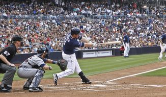 San Diego Padres' Jedd Gyorko lofts a sacrifice fly to left field that scores Chris Denorfia from third in the first inning of a baseball game against the Detroit Tigers Saturday, April 12, 2014, in San Diego. (AP Photo/Lenny Ignelzi )