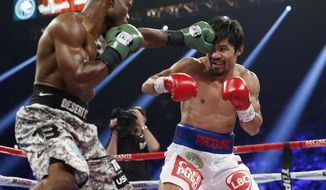 Timothy Bradley, left, lands a left to the head of Manny Pacquiao, of the Philippines, in their WBO welterweight title boxing fight Saturday, April 12, 2014, in Las Vegas. (AP Photo/Eric Jamison)