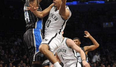 Brooklyn Nets' Jorge Gutierrez (13) takes aim for the basket around Orlando Magic's Andrew Nicholson (44) during the first half of an NBA basketball game Sunday, April 13, 2014, in New York. (AP Photo/Kathy Kmonicek)
