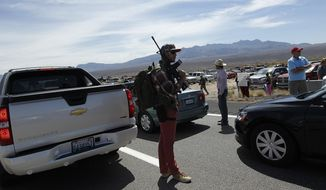 Tyler Lewis, from St. George, Utah, stands in the middle of north bound I-15 with his gun near Bunkerville, Nev. while gathering with other supporters of the Bundy family to challenge the Bureau of Land Management on April 12, 2014. (AP Photo/Las Vegas Review-Journal, Jason Bean)