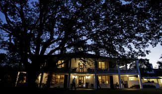 Workers wait outside of the Augusta National Golf Clubhouse in the early morning before the fourth round of the Masters golf tournament Sunday, April 13, 2014, in Augusta, Ga. (AP Photo/Darron Cummings)
