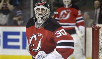 As fellow goalie Cory Schneider, background, looks on, New Jersey Devils goalie Martin Brodeur warms up in the goal before an NHL hockey game against the Boston Bruins in Newark, N.J., Sunday, April 13, 2014. (AP Photo/Mel Evans)