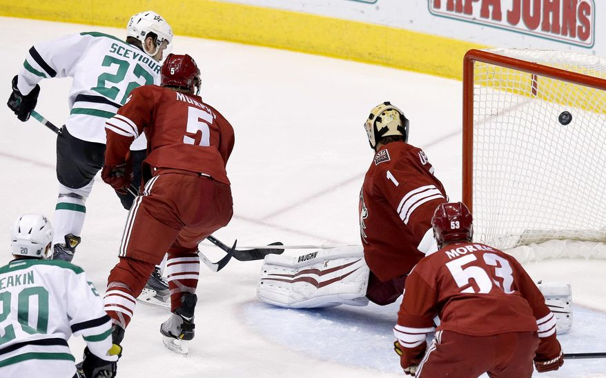 Dallas Stars' Colton Sceviour (22) scores as he sends the puck past Phoenix Coyotes' Thomas Greiss (1), of Germany, as Coyotes' Connor Murphy (5) defends and Coyotes' Derek Morris (53) and Stars' Cody Eakin (20) look on during the first period of an NHL hockey game on Sunday, April 13, 2014, in Glendale, Ariz. (AP Photo/Ross D. Franklin)