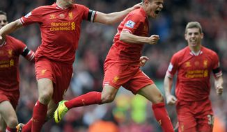 Liverpool's Philippe Coutinho right, celebrates with team-mate Steven Gerrard left, after he scores the third goal of the game for his side during their English Premier League soccer match against Manchester City at Anfield in Liverpool, England, Sunday April. 13, 2014. (AP Photo/Clint Hughes)