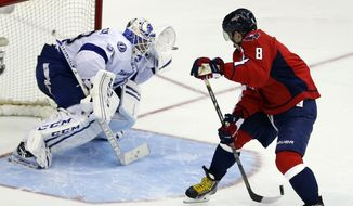 Washington Capitals right wing Alex Ovechkin, right, from Russia, shoots the puck behind his back against Tampa Bay Lightning goalie Anders Lindback, from Sweden, in the shootout portion of an NHL hockey game on Sunday, April 13, 2014, in Washington. Lindback blocked the shot and the Lightning won 1-0 in a shootout. (AP Photo/Alex Brandon)
