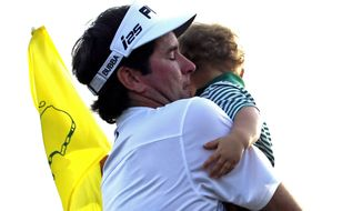 Bubba Watson carries his son Caleb after winning the Masters golf tournament Sunday, April 13, 2014, in Augusta, Ga. (AP Photo/Matt Slocum)