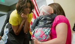 First lady Michelle Obama meets with six-month-old Kyleigh Garmon, and her mother Megan Garmon, from Alabama, during her visit to the Wounded Warriors being cared for at the Fisher House at Walter Reed National Military Medical Center in Bethesda, Md., Monday, April 14, 2014. The first lady is participating in a pre-Easter celebration with military families and their children. The Fisher House provides extend stay housing program for family members while their loved ones receiving specialized medical care at Walter Reed. (AP Photo/Pablo Martinez Monsivais)