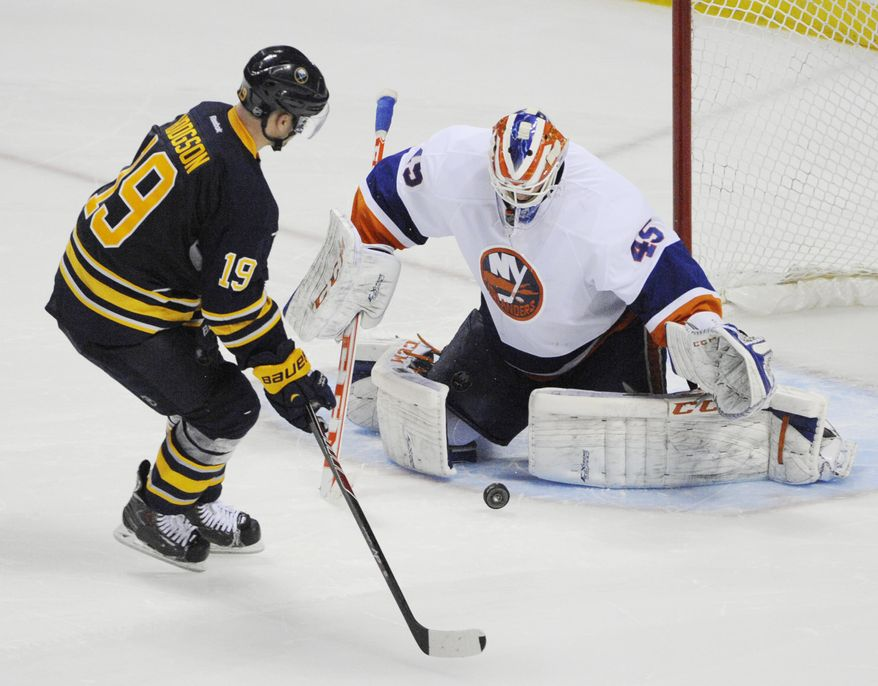 The shot by Buffalo Sabres' Cody Hodgson (19) gets stopped by New York Islanders' Anders Nilsson (45), of Sweden, during the team shootout during an NHL hockey game in Buffalo, N.Y., Sunday April 13, 2014. New York won 4-3.  (AP Photo/Gary Wiepert)