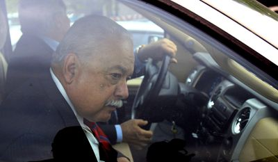 Former Hidalgo County Sheriff Lupe Trevino leaves the McAllen Federal Court building with his attorney Robert Yzaguirre, Monday, April 14, 2014, in McAllen, Texas. Trevino pleaded guilty Monday to money laundering and faces a 20-year sentence. He was released on a $30,000 unsecured bond Monday. (AP Photo/The Monitor, Gabe Hernandez)