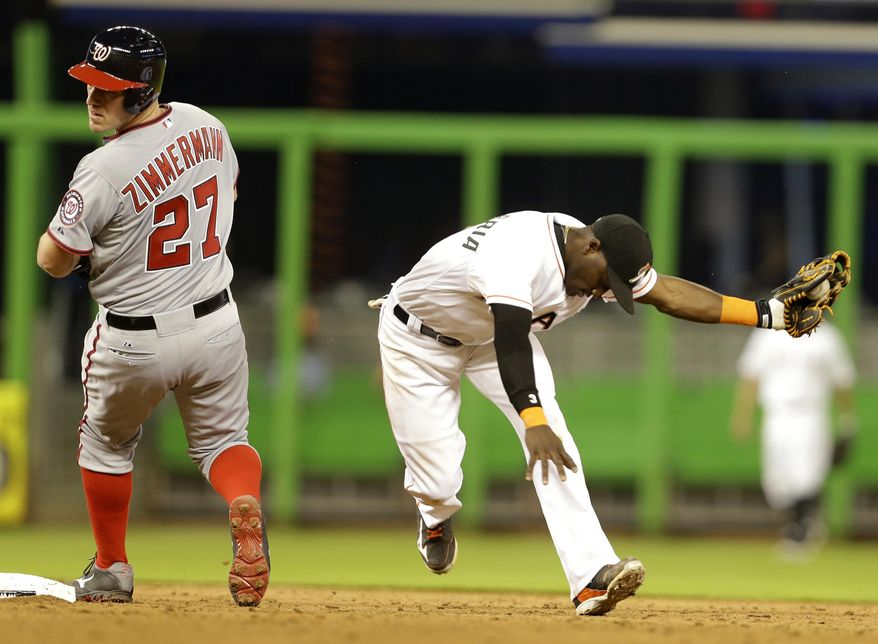 Washington Nationals' Jordan Zimmermann (27) looks behind as he is out at second as  Miami Marlins shortstop Adeiny Hechavarria takes the throw during the sixth inning of the MLB National League baseball game, Monday, April 14, 2014, in Miami. (AP Photo/Lynne Sladky)