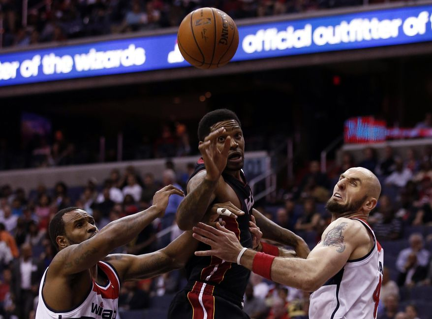 Washington Wizards forward Trevor Booker, left, Miami Heat forward Udonis Haslem, middle, and Wizaards center Marcin Gortat, from Poland, go for a rebound in the first half of an NBA basketball game, Monday, April 14, 2014, in Washington. (AP Photo/Alex Brandon)