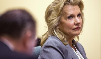 FILE - In this on Feb. 10, 2014, file photo, Kathleen Winn, listens to arguments from Yavapai Deputy County Attorney Benjamin Kreutzberg, during a hearing in Phoenix, Ariz. Arizona administrative law judge Tammy Eigenheer ruling to consider whether Republican Attorney General Tom Horne illegally coordinated campaign spending with an aide Kathleen Winn running an independent group during his 2010 election bid, is set to release her ruling on Monday, April 14, 2014. (AP Photo/The Arizona Republic, Tom Tingle, File)  MARICOPA COUNTY OUT; MAGS OUT; NO SALES