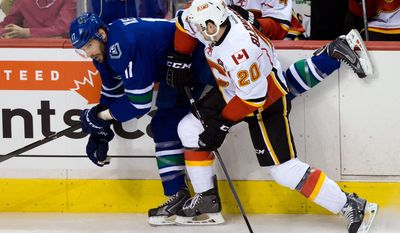 Calgary Flames' Curtis Glencross, right, checks Vancouver Canucks' Ryan Kesler during first period NHL hockey action in Vancouver, British Columbia, on Sunday April 13, 2014. (AP Photo/The Canadian Press, Darryl Dyck)