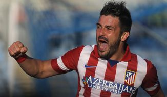 Atletico's  David Villa celebrates Diego Godin's goal during a Spanish La Liga soccer match between Getafe and Atletico Madrid at the Coliseum Alfonso Perez  stadium in Madrid, Spain, Sunday, April 13, 2014. (AP Photo/Andres Kudacki)