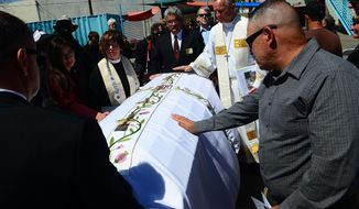 Christopher Sedillo, right ,touches the casket of James Boyd, the homeless man who was fatally shot last month by Albuquerque police officers in the Sandia Foothills.  A memorial was held for Boyd at St Martin's Hospitality Center in Albuquerque, N.M., Saturday April 13, 2014. (AP Photo/Albuquerque Journal, Adolphe Pierre-Louis)