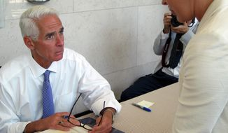 Former Republican Gov. Charlie Crist signs a copy of his book before he speaks to the Forum Club of the Palm Beaches in West Palm Beach, Fla., Monday April 14, 2014. Crist aspires to return as governor as a Democrat. (AP Photo/Matt Sedensky)