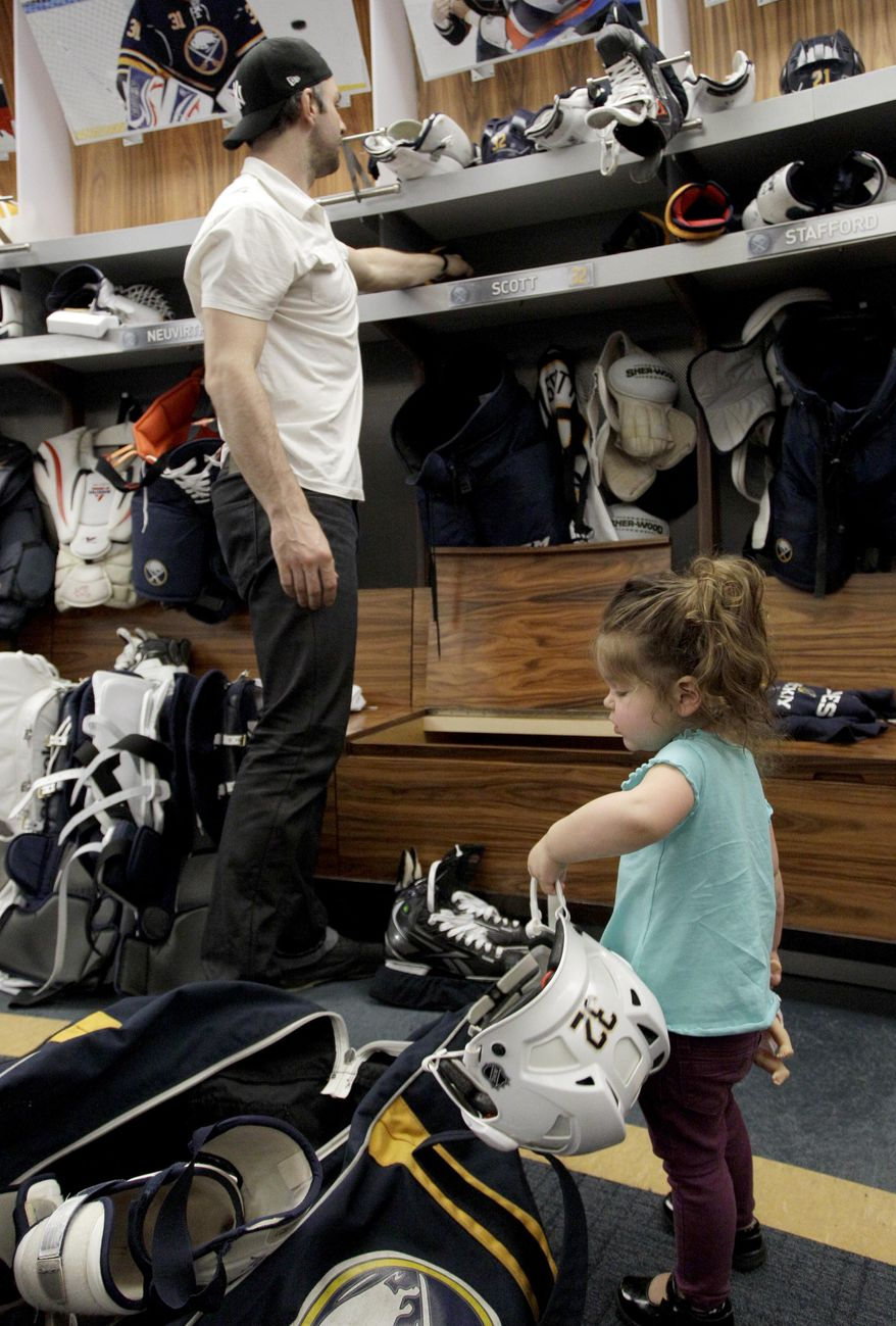 Buffalo Sabres left wing John Scott gets help cleaning out his locker from daughter Eva, 2, after players gathered for the last time on Monday, April 14, 2014, after the NHL hockey team clinched the NHL's worst record in Buffalo, N.Y. (AP Photo/Nick LoVerde)