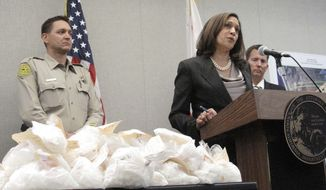 California Attorney General Kamala Harris, center, announces the takedown of a California-based drug trafficking organization during a news conference Monday, April 14, 2014, in Fresno, Calif. On the table are bags of crystal methamphetamine that authorities say the organization smuggled in along with cocaine from Mexico. Once in the Central Valley of California, officials say the drugs were distributed across the United States. At the left is King County Sheriff Dave Robinson and to the far right is Tulare County District Attorney Tim Ward. (AP Photo/Scott Smith)