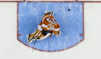Carolina Hurricanes' Eric Staal, bottom, shoots the puck past Philadelphia Flyers' Cal Heeter, top, for a goal during the shootout of an NHL hockey game, Sunday, April 13, 2014, in Philadelphia. The Hurricanes won 6-5. (AP Photo/Chris Szagola)