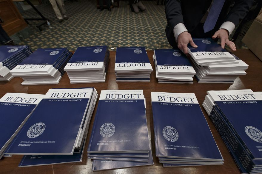 FILE - This March 4, 2014 file photo shows copies of President Barack Obama's proposed fiscal 2015 budget set out for distribution on Capitol Hill in Washington. The Congressional Budget Office releases its analysis of President Barack Obama's 2015 budget proposal, including the effects of the insurance coverage provisions of the health law, along with updated 10-year projections of federal spending, revenues and deficits.  (AP Photo/J. Scott Applewhite, File)