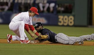 Atlanta Braves' Justin Upton right, steals second as Philadelphia Phillies' Chase Utley makes a late tag in the third inning of a baseball game Monday, April 14, 2014, in Philadelphia.  (AP Photo/H. Rumph Jr)