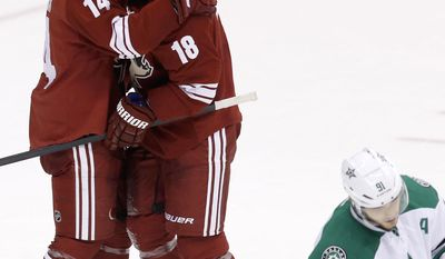 Phoenix Coyotes' David Moss (18) celebrates his goal with teammate Jeff Halpern (14) as Dallas Stars' Tyler Seguin (91) skates away during the third period of an NHL hockey game on Sunday, April 13, 2014, in Glendale, Ariz.  The Coyotes defeated the Stars 2-1. (AP Photo/Ross D. Franklin)