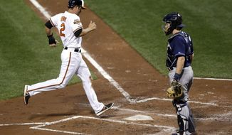 Baltimore Orioles' J.J. Hardy jogs to home plate in front of Tampa Bay Rays catcher Ryan Hanigan on a single by Ryan Flaherty in the second inning of a baseball game, Monday, April 14, 2014, in Baltimore. (AP Photo/Patrick Semansky)