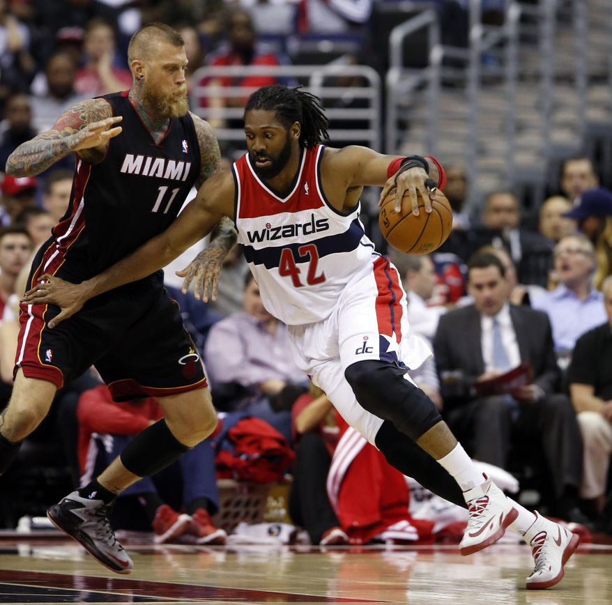 Washington Wizards forward Nene (42), from Brazil, drives against Miami Heat forward Chris Andersen (11) in the first half of an NBA basketball game, Monday, April 14, 2014, in Washington. (AP Photo/Alex Brandon)