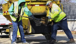 In this March 20, 2014 photo, Peru public works workers Andy Dellinger, left, and Ron Franklin patch potholes in Peru, Ill. When the mercury rises and the ice recedes, revealing miles of pothole-riddled road, local patching crews hit the streets with stop-gap efforts to make the lanes safer.  (AP Photo/NewsTribune, Chris Yucus)