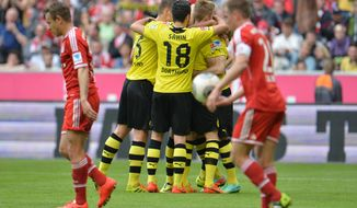 Dortmund players celebrate after scoring during the Bundesliga soccer match between FC Bayern Munich and Borussia Dortmund in Munich, Germany, on Saturday, April 12, 2014. (AP Photo/Kerstin Joensson)