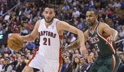 Toronto Raptors' Greivis Vasquez, left, drives past Milwaukee Bucks' Ramon Sessions during first half NBA basketball action in Toronto on Monday, April 14, 2014. (AP Photo/The Canadian Press, Chris Young)