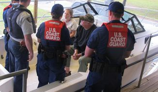 Personnel from the U.S. Coast Guard and the Royal Canadian Mounted Police participate in a boat boarding exercise at the Federal Law Enforcement Training Center in Charleston, S.C., on Tuesday, April 15, 2014. The personnel are training for the Shiprider program, a joint effort in which law enforcement personnel from both agencies ride on the same boats to patrol the border between the United States and Canada. (AP Photo/Bruce Smith)