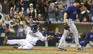 San Diego Padres' Seth Smith slides in with the go ahead run as Colorado Rockies relief pitcher Rex Brothers walks away after two runs scored on a wild pitch and a throwing error in the eighth inning of a baseball game won 5-4 by the Padres Monday, April 14, 2014, in San Diego. (AP Photo/Lenny Ignelzi